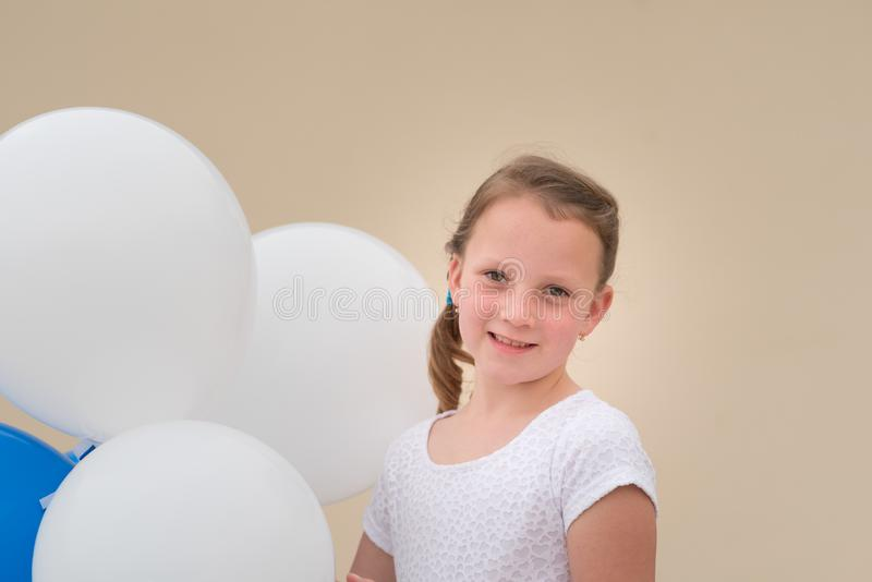 Gl?ckliches kleines M?dchen mit den blauen und wei?en Ballonen lizenzfreie stockfotografie