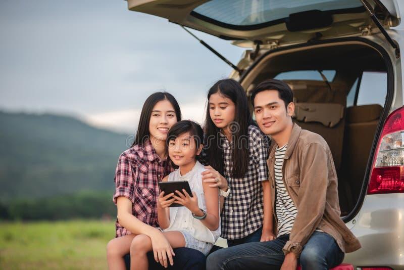 Gl?ckliches kleines M?dchen mit der asiatischen Familie, die im Auto f?r das Genie?en von Autoreise- und Sommerferien im Reisemob lizenzfreie stockbilder