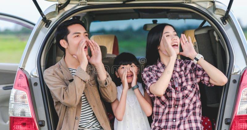 Gl?ckliches kleines M?dchen mit der asiatischen Familie, die im Auto f?r das Genie?en von Autoreise- und Sommerferien im Reisemob stockbild