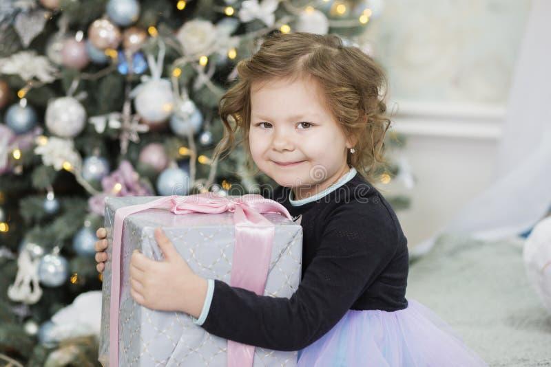 Gl?ckliches kleines M?dchen mit Weihnachtsgeschenk M?dchen erfreut mit Geschenk Nettes Kind, das sich nach Hause f?r Weihnachtsfe lizenzfreie stockfotos