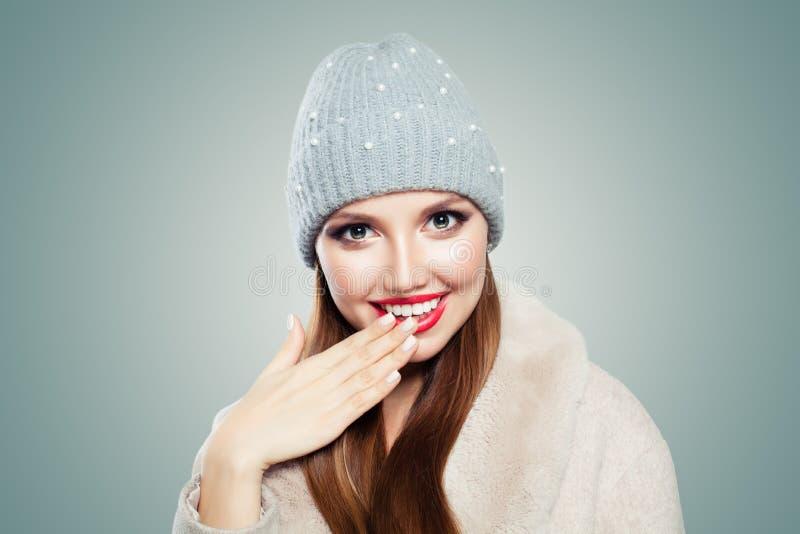 Gl?ckliches Lachen der jungen Frau Hübsches vorbildliches Mädchen im grauen Hut auf weißem Hintergrund stockbilder