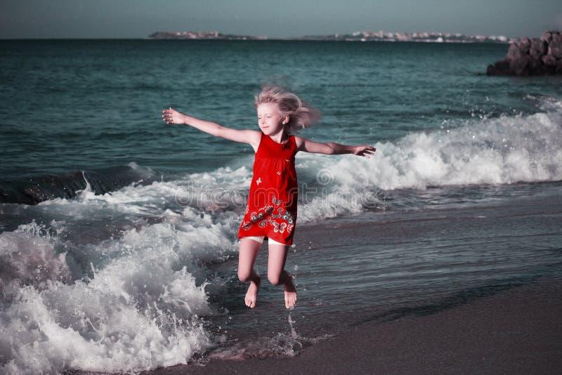Gl?ckliches M?dchen im farbigen Kleid, das auf die Wellen auf dem Strand springt lizenzfreies stockbild