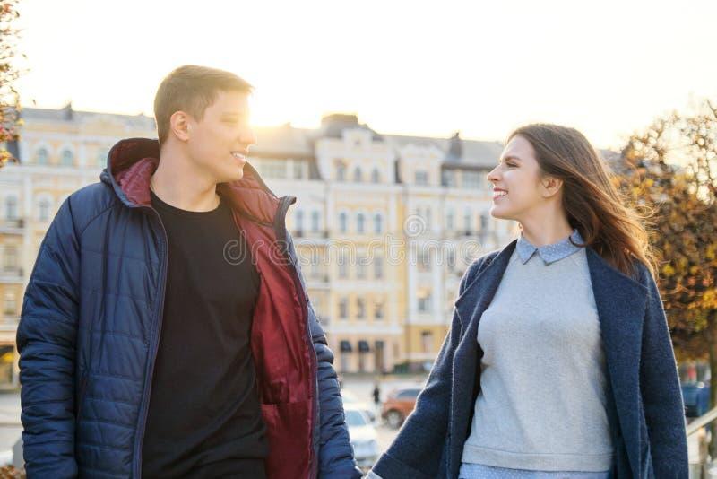 Gl?ckliches Mann- und Frauenh?ndchenhalten der jungen Paare lizenzfreie stockbilder