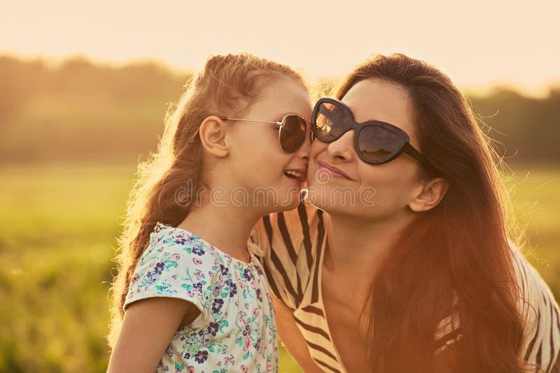 Gl?ckliches Modekinderm?dchen, das ihre Mutter das Geheimnis in der modischen Sonnenbrille in der Profilansicht fl?stert und auf  lizenzfreies stockfoto