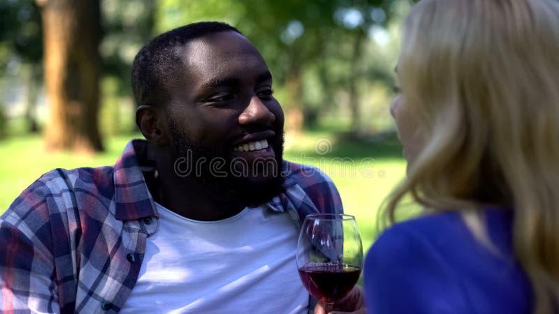 Gl?ckliches Paar, das den teuren alten Wein, gealterten Alkohol im Park genie?end, Datum trinkt stockfoto