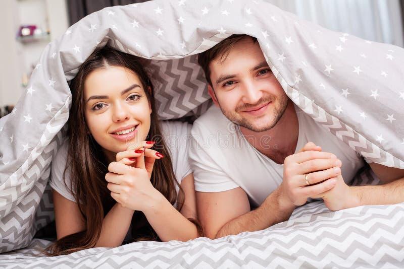 Gl?ckliches Paar, das Spa? im Bett hat Vertraute sinnliche junge Paare im Schlafzimmer, das sich am?siert lizenzfreie stockfotografie