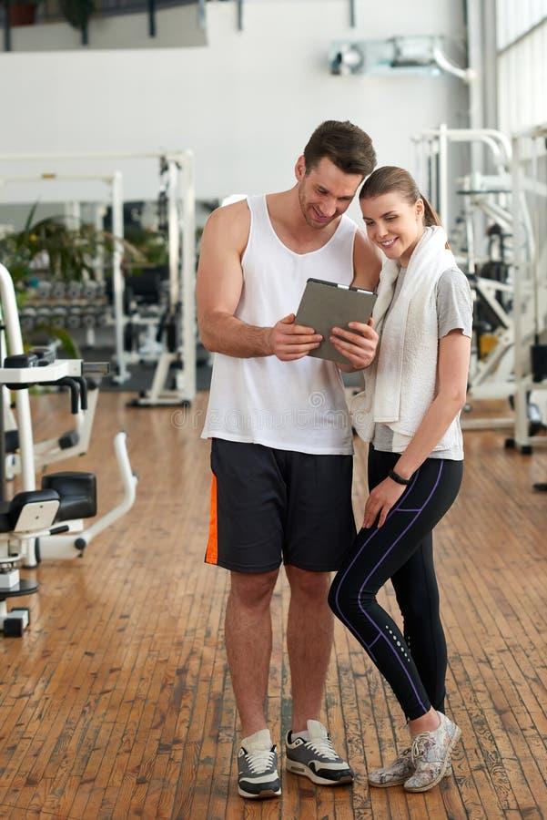 Gl?ckliches Paar, das Tablette im Fitness-Club verwendet stockfotografie