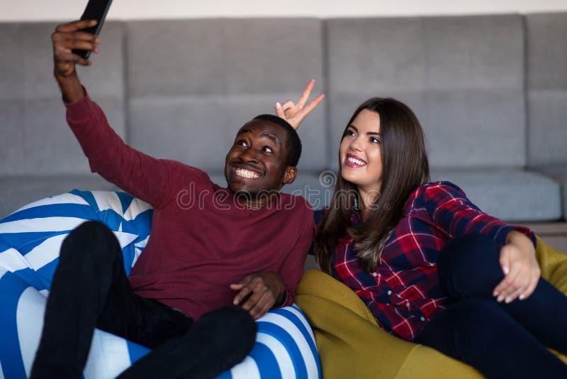 Gl?ckliches Paar mit Computer Tablette und Smartphone auf einem Sofa lizenzfreie stockbilder