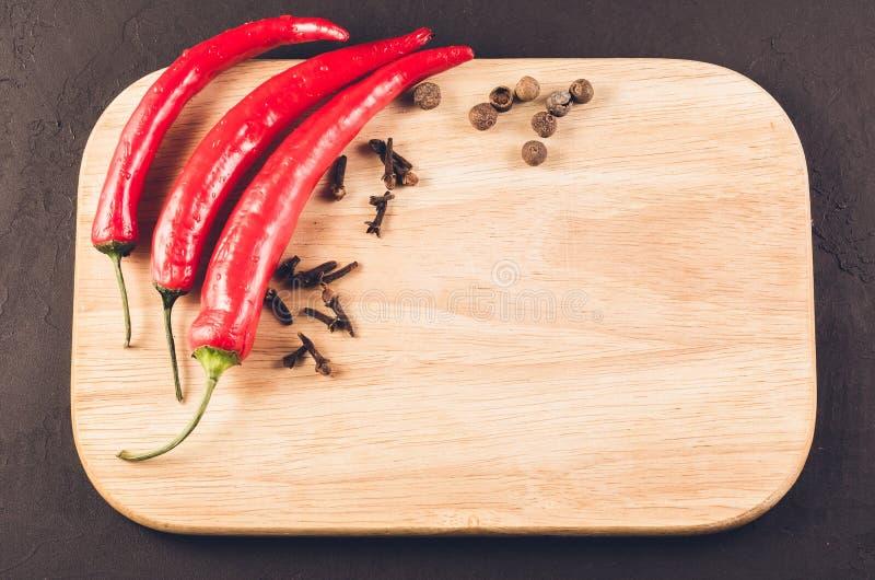 Gl?dheta peppar och kryddor p? en tom sk?rbr?da/gl?dheta chilipeppar och kryddor f?r chili p? en tom sk?rbr?da p? ett m?rker arkivfoton