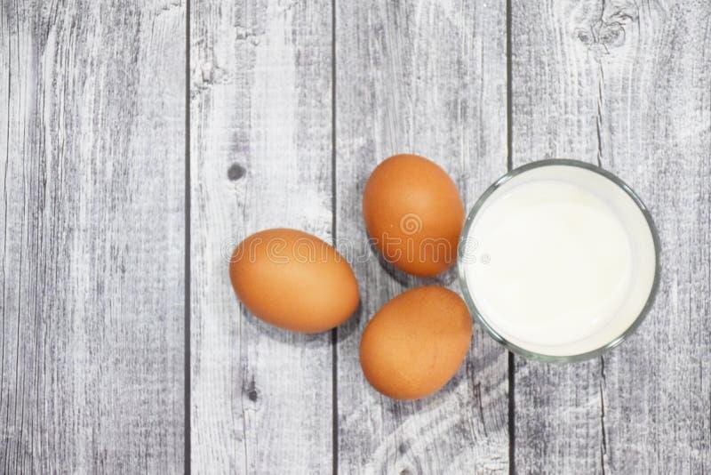 3 Gl?ser Milch und Eier, auf einem grauen h?lzernen Hintergrund, Nahrunggetr?nkehintergrund lizenzfreie stockfotografie