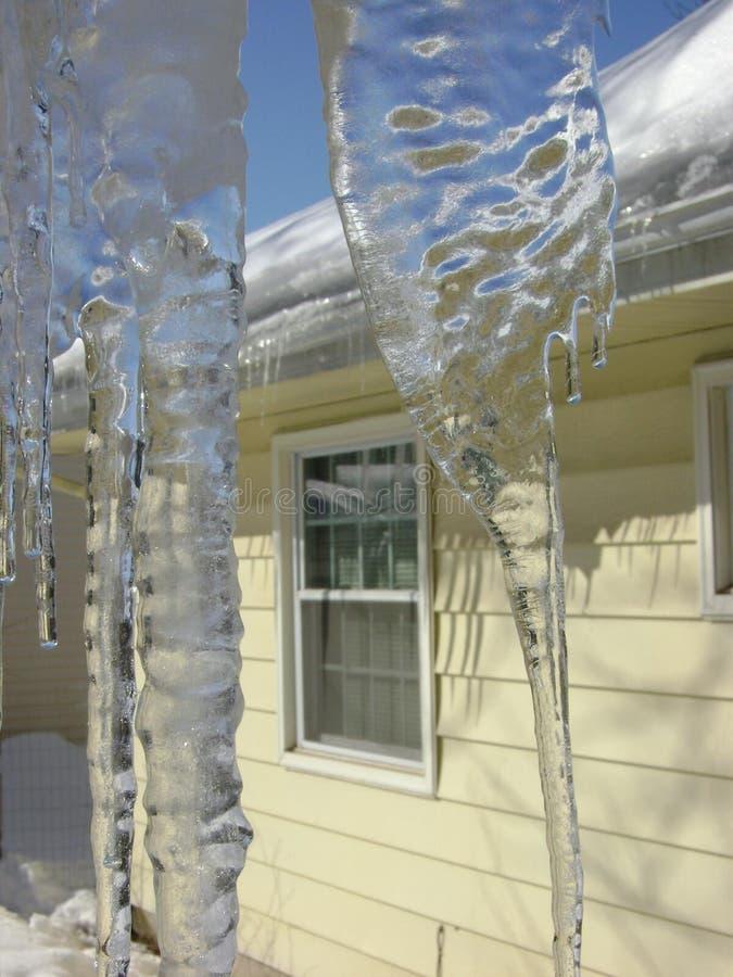 Glaçons à nervures épais sur le toit par la fenêtre images stock