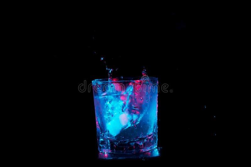 Glaçons éclaboussant dans les roches un verre de liquide sous les lumières colorées d'isolement sur un fond noir photos stock
