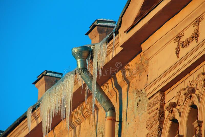 Glaçons éclatants pendant du toit photographie stock libre de droits