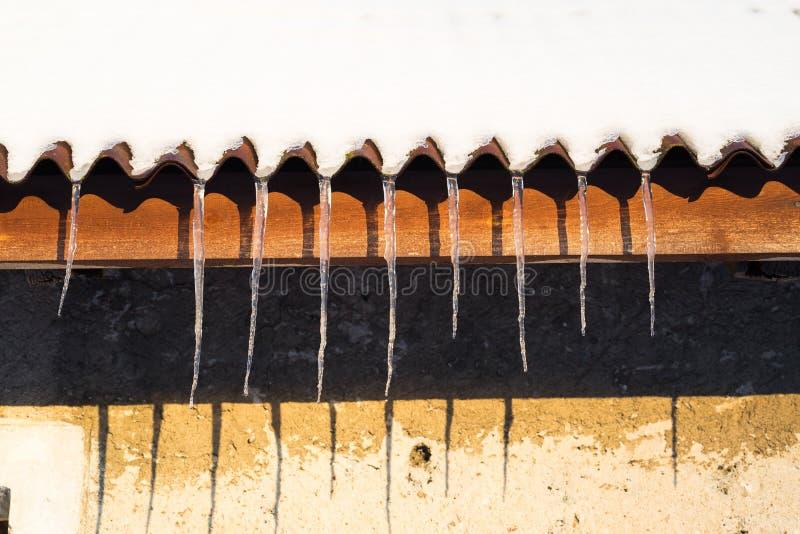 Glaçons accrochant sur le toit à l'hiver image stock