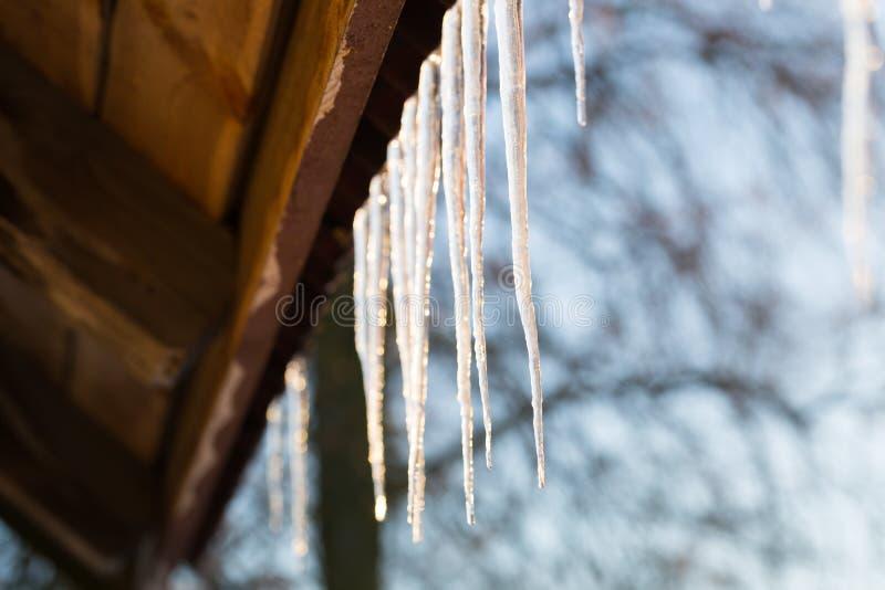 Glaçons accrochant sur le toit à l'hiver photo stock