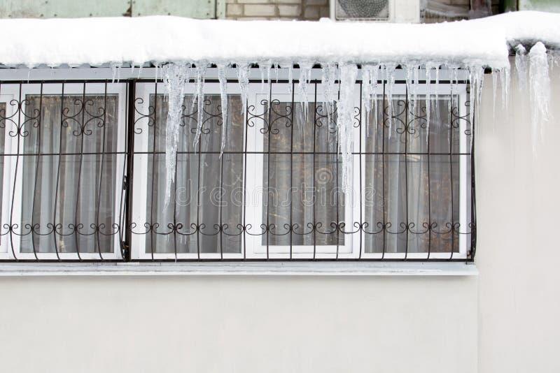 Glaçons accrochants dangereusement du toit au-dessus de la fenêtre avec une barrière en hiver photographie stock libre de droits
