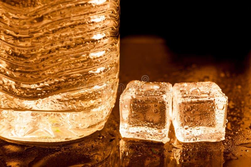 glaçons avec de l'eau potable dans le fond clair d'or images libres de droits
