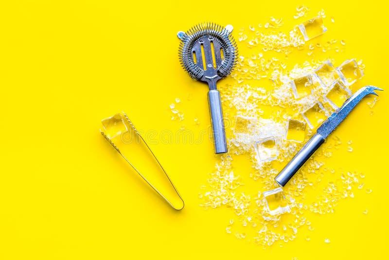 Glaçons brisés avec des outils de barman sur la vue supérieure jaune de table de cuisine photo stock