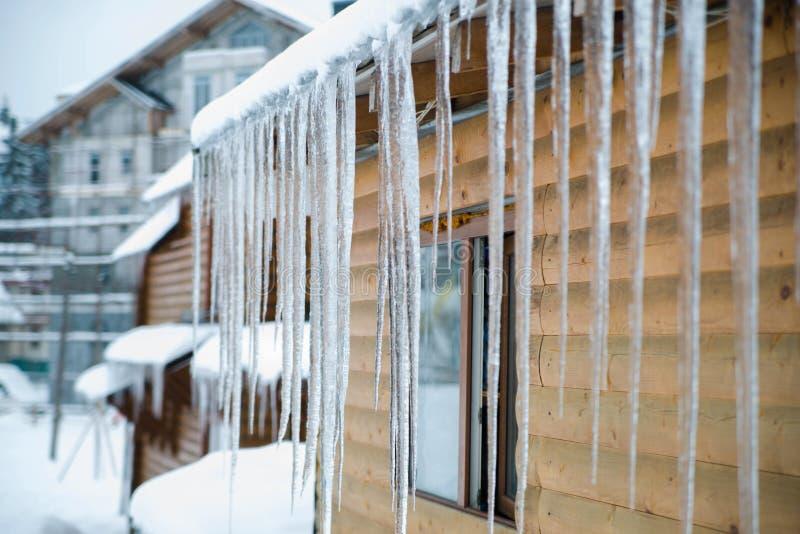 Glaçons d'hiver accrochant sur le toit de maison de campagne images libres de droits