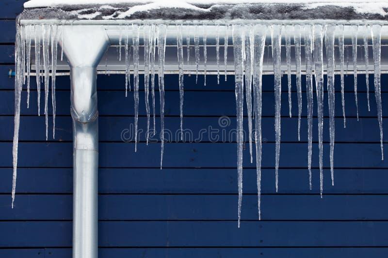 Glaçons sur le toit Concept de l'hiver downspout Fond en bois bleu images libres de droits