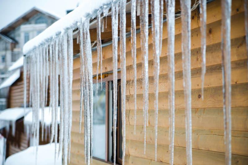 Glaçons sur le toit Concept de l'hiver Fond en bois jaune images stock