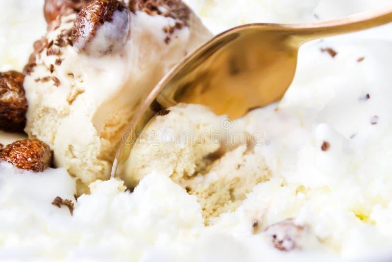 Glace à la vanille avec du chocolat et des miettes avec la cuillère de cuivre Le processus d'interrompre une boule de la crème gl photos libres de droits