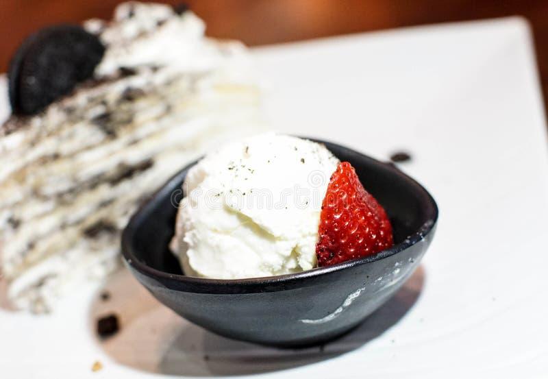 Glace à la vanille avec une tranche de gâteau de crêpe photos libres de droits