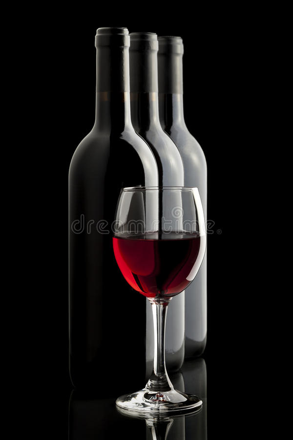 Glace élégante de vin rouge et une bouteille de vin photo stock