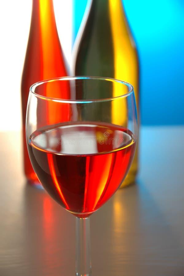 Glace de vin et 2 bouteilles photo stock