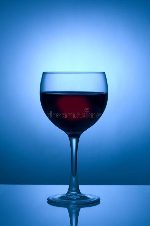 Glace de vin silhouettée contre le projecteur bleu image stock