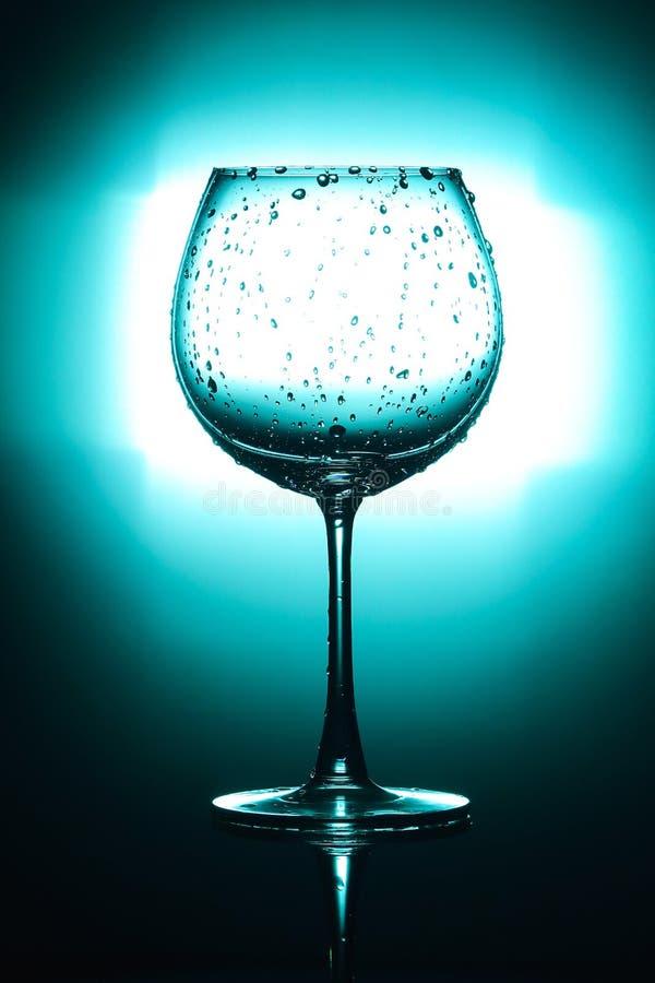 Glace de vin vide d'isolement sur le fond vert clair et noir images libres de droits
