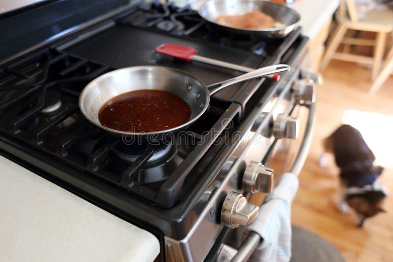 Glace Demi eller brun glasyr som lagar mat i en rostfritt stålkastrull arkivfoto