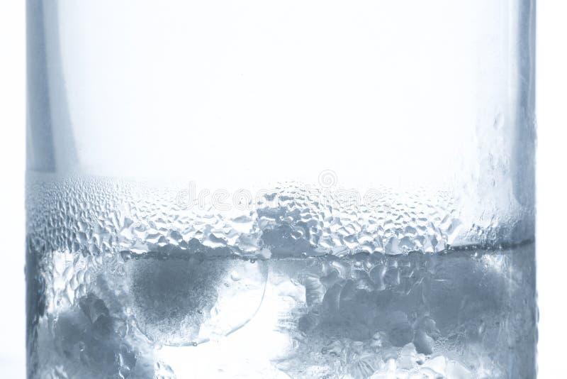 Glace fondant dans le verre de l'eau avec la condensation des côtés image libre de droits