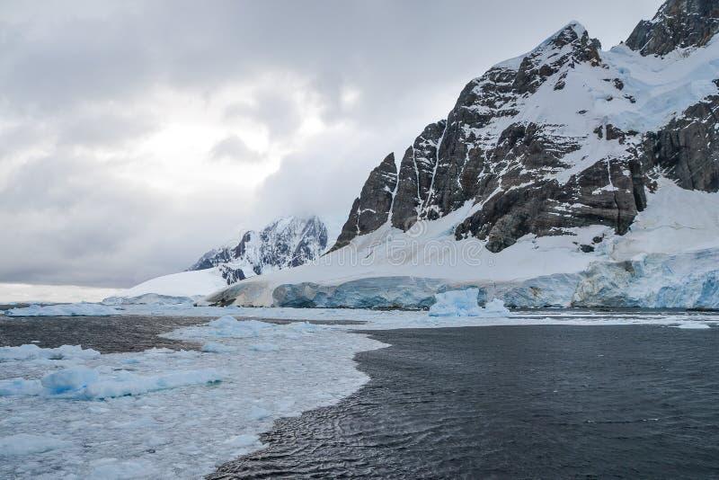 Glace fondant devant le glacier et la montagne antarctiques photo stock