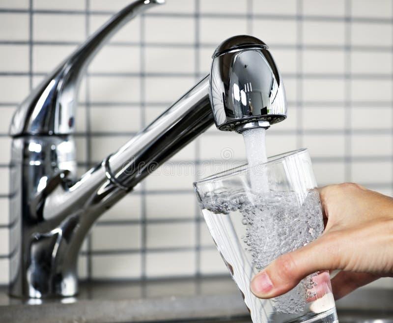 Glace remplissante d'eau du robinet photographie stock