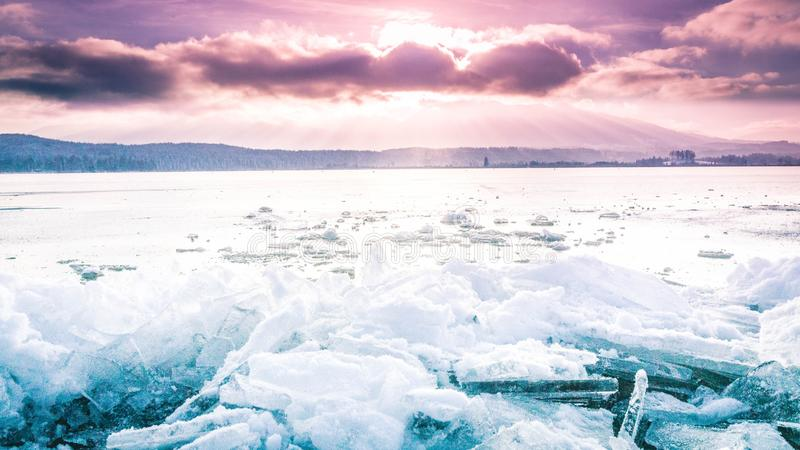 Glace sur une surface gelée avec le ciel nuageux pourpre stupéfiant à l'arrière-plan photo stock