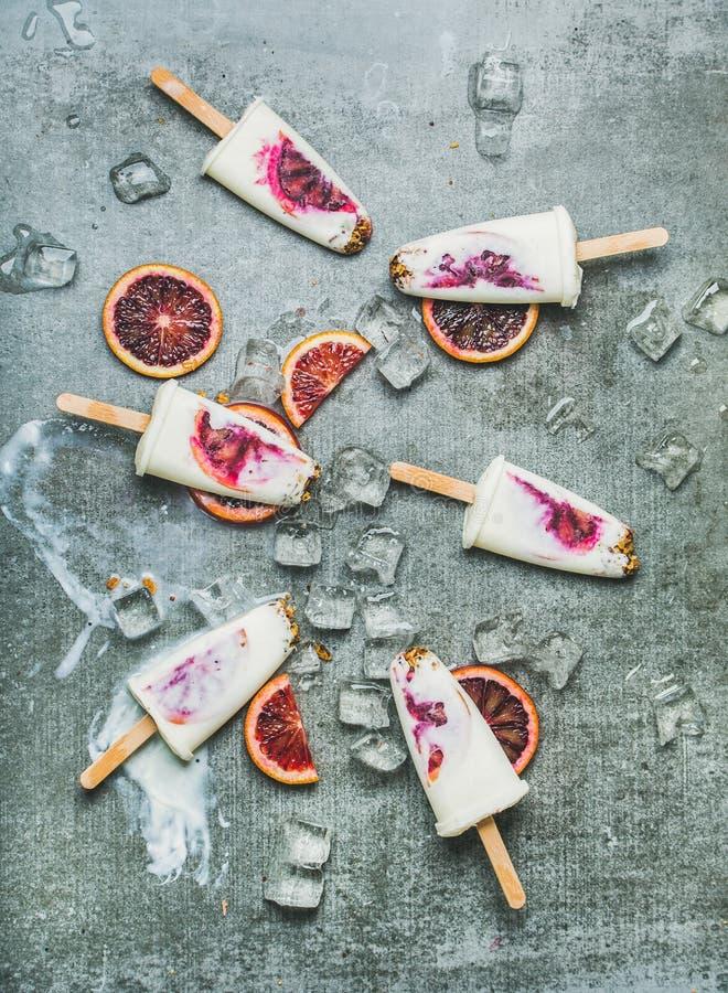 Glaces à l'eau d'orange sanguine, de yaourt et de granola sur la glace, fond concret images stock