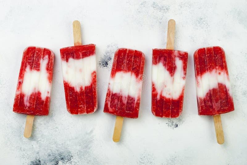 Glaces à l'eau faites maison de lait de noix de coco de fraise de vegan - glace saute - paletas sur le fond blanc rustique photos libres de droits