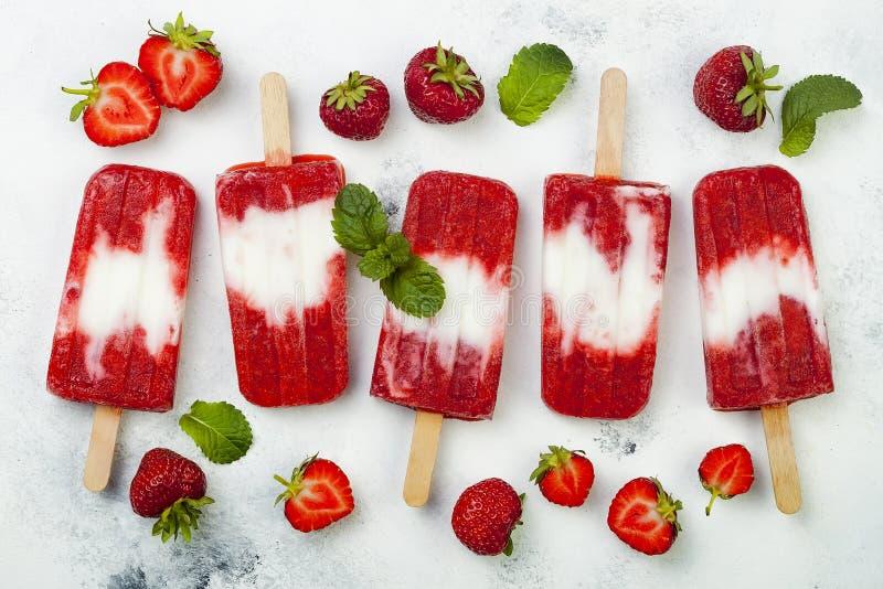 Glaces à l'eau faites maison de lait de noix de coco de fraise de vegan - glace saute - paletas sur le fond blanc rustique photographie stock