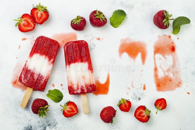 Glaces à l'eau faites maison de lait de noix de coco de fraise de vegan - glace saute - paletas sur le fond blanc rustique photos stock
