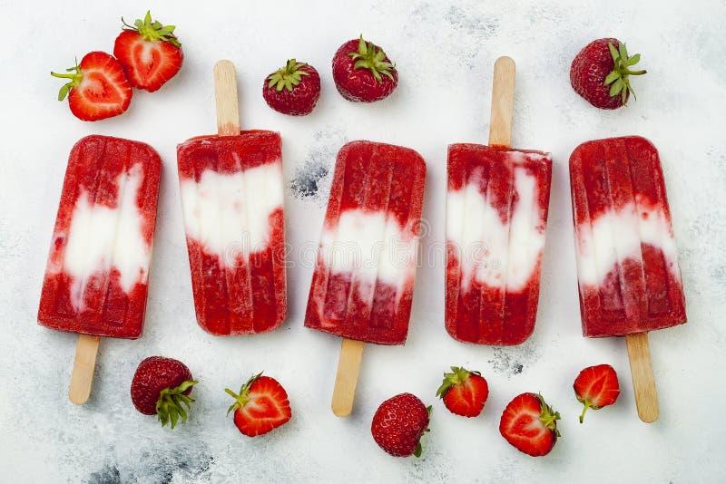 Glaces à l'eau faites maison de lait de noix de coco de fraise de vegan - glace saute - paletas sur le fond blanc rustique images stock