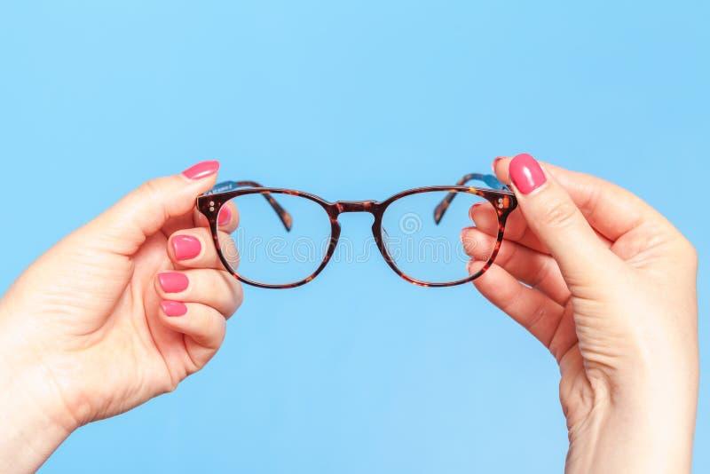 Glaces de relev? modernes La femme prend des lunettes d'optique image stock
