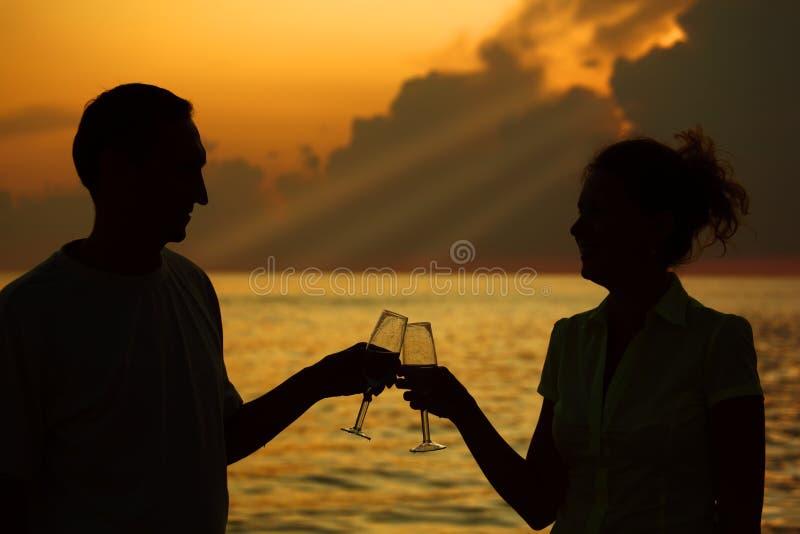 Glaces de taule d'homme et de femme. Silhouettes sur la mer photos libres de droits