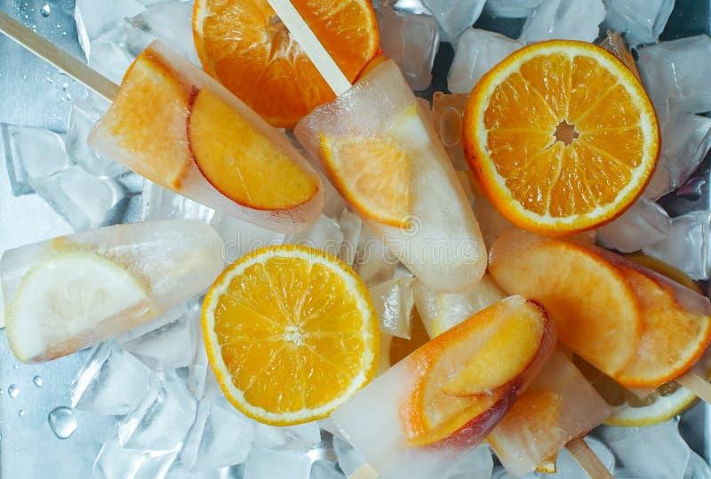 Glaces ? l'eau faites maison d'orange et de p?che avec des tranches de glace et d'agrume sur le fond clair photographie stock