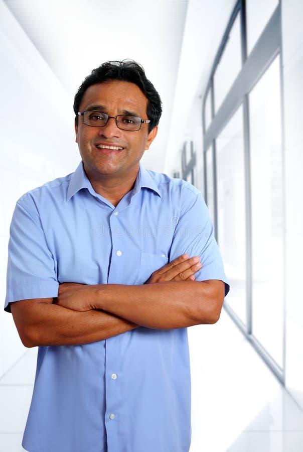 Glaces latines indiennes d'homme d'affaires dans le bureau photo libre de droits