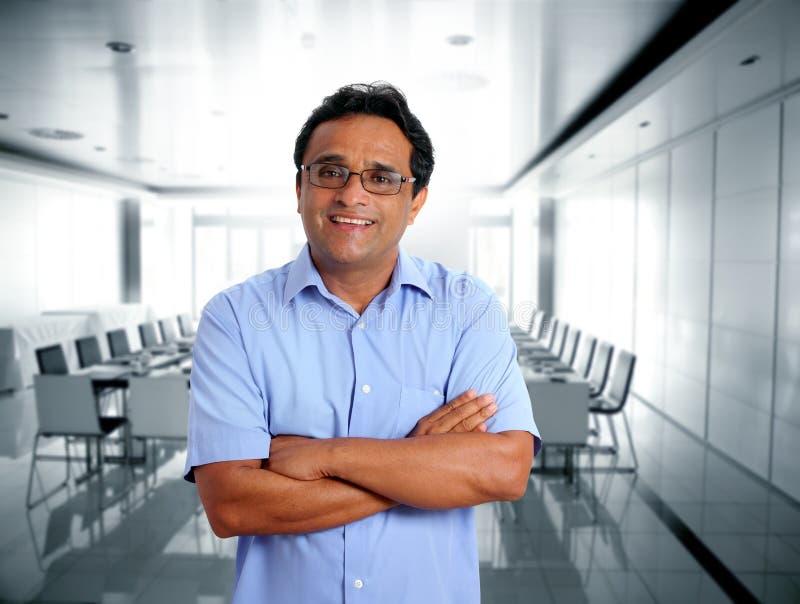 Glaces latines indiennes d'homme d'affaires dans le bureau photos stock