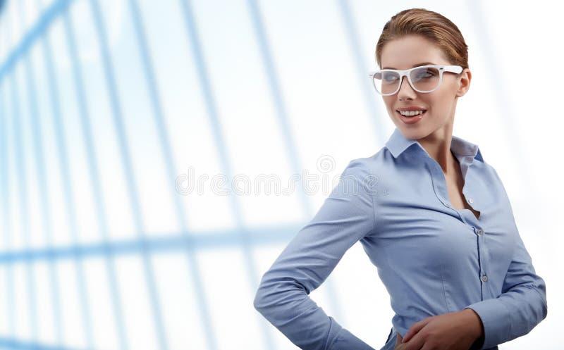 Glaces s'usantes de femme dans le bureau images stock