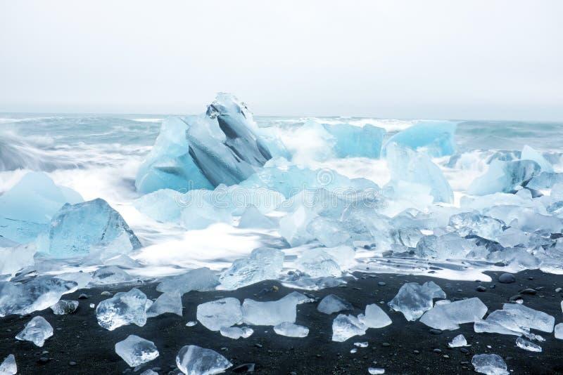 Glacez les roches sur une plage noire de sable en Islande photo stock