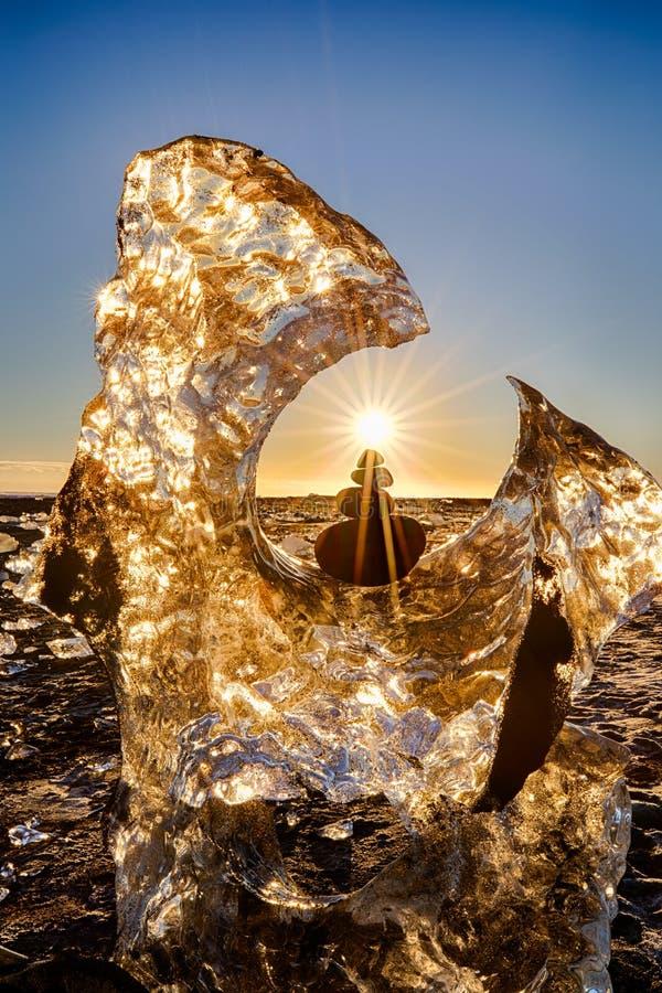 Glaciären och allsidigt vaggar med solstjärnan på Island Diamond Beach med svart sand royaltyfri fotografi