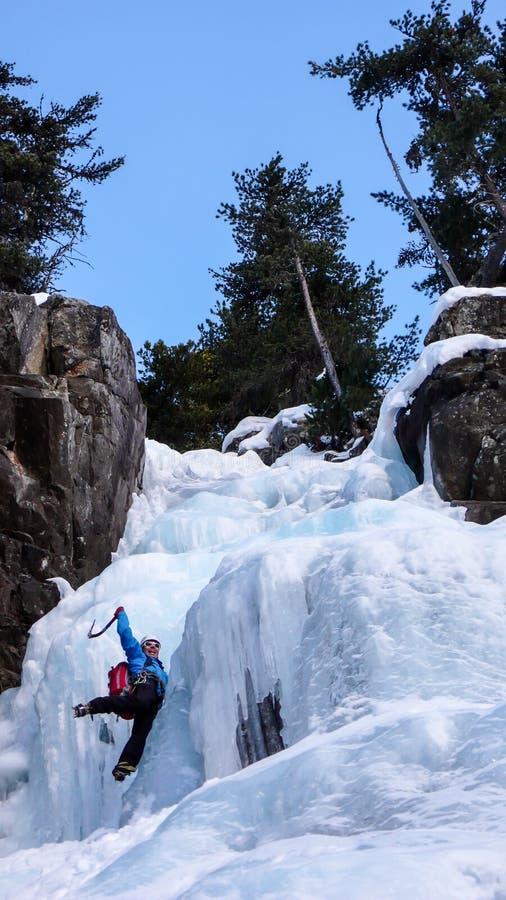 Glaciériste masculin dans une veste bleue sur une cascade congelée magnifique s'élevant dans les Alpes en hiver profond photographie stock libre de droits